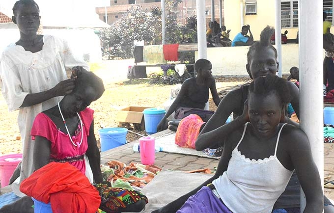 Women from Aweil fix each other's hair as they prepare to go home after their fistula repair surgery.