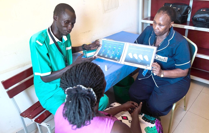 Midwife Peter Door explains family planning methods to a mother at a clinic in Rumbek.